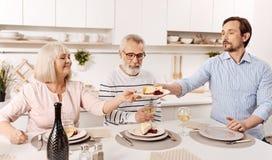 Charyzmatyczny mężczyzna cieszy się rodzinnego gościa restauracji z rodzicami w domu Obrazy Stock