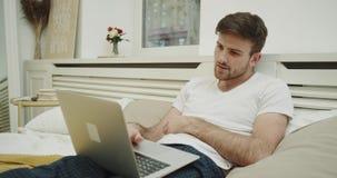 Charyzmatyczny młody człowiek patrzeje przez laptopu, pracuje w wygodnym łóżku 4K Strzelający na Czerwonej epopei zdjęcie wideo