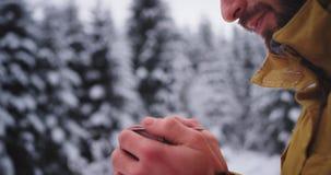 Charyzmatyczny turystyczny portret zamarznięte czerwieni ręki w ciężkiej zimie po środku lasu pije niektóre gorącej herbaty dosta zdjęcie wideo