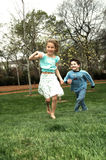 The Chase. Two children play the game of chase up a grassy hill. Running with motion Royalty Free Stock Photo