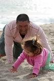 Chase the Baby. Father playing with his daughter at the beach *child has slight motion blur. father completely in focus royalty free stock photos