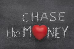 Chase the money heart. Chase the money phrase handwritten on blackboard with heart symbol instead of O Stock Photography