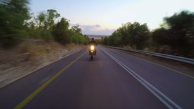 Chase view of a fast motorcycle driving on a curved road. Fast motorcycle driving on a curved road at high speed stock video footage