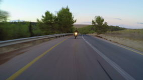 Chase view of a fast motorcycle driving on a curved road. Fast motorcycle driving on a curved road at high speed stock video