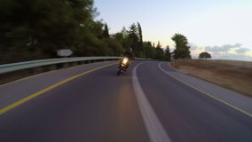 Chase view of a fast motorcycle driving on a curved road. Fast motorcycle driving on a curved road at high speed stock footage
