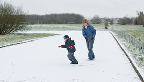 Chased in the snow. Mother playing with her son in the snow Royalty Free Stock Image