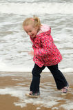 Chased by the waves. Young girl smiling as shes being chased by the waves on a chilly day at the beach royalty free stock image