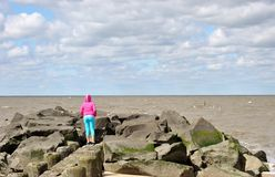 Chasing the birds. A girl on the jetty chasing the birds from the rocks Royalty Free Stock Photo
