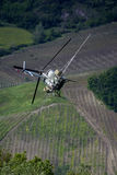 Chasing the spraying helicopter. Chemical treatments by helicopter over the vineyards. Italy, Oltrepo pavese hills Stock Photo