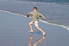 Chasing Waves. Young boy chasing waves on the beach on a sunny day royalty free stock photography
