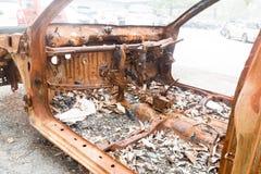Chasis oxidado de un coche quemado abandonado por el lado de la calle Fotos de archivo libres de regalías