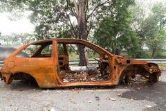 Chasis oxidado de un coche quemado abandonado por el lado de la calle Imágenes de archivo libres de regalías