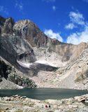 Chasm Lake. Three hikers view Chasm Lake, at the base of Longs Peak, Rocky Mountain National Park, Colorado Royalty Free Stock Photography
