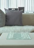 Chass cristalinos en naxe de la tabla al sofá en sala de estar imagen de archivo