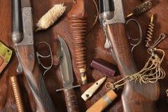 Chassant le concept avec le fusil de chasse, le couteau et les munitions pour chasser dispos?e sur le fond brun images stock