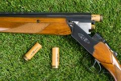 Chassant le concept de fusil et de cartouches, sur un fond d'herbe verte Image stock