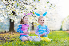 Chasse à oeuf de pâques Enfants avec le jardin d'oreilles de lapin au printemps Photo stock