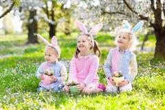 Chasse à oeuf de pâques Enfants avec les oreilles et le panier de lapin Photo stock