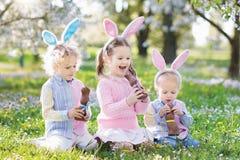 Chasse à oeuf de pâques de jardin Les enfants mangent du chocolat de lapin Photographie stock libre de droits