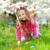 Chasse adorable de petite fille pour l'oeuf de pâques le jour de Pâques Image libre de droits