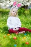 Chasse adorable de petite fille pour l'oeuf de pâques le jour de Pâques Image stock