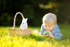Chasse avec du charme de petit garçon pour le parc d'oeuf de pâques au printemps le jour de Pâques Photos libres de droits