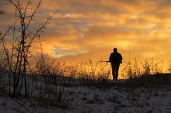 Chasse d'hiver au lever de soleil Chasseur se déplaçant avec le fusil de chasse photos libres de droits