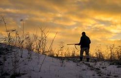 Chasse d'hiver au lever de soleil Chasseur se déplaçant avec le fusil de chasse images libres de droits