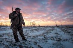 Chasse d'hiver au lever de soleil Chasseur se d?pla?ant avec le fusil de chasse photo stock