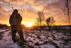 Chasse d'hiver pour des lièvres au lever de soleil Chasseur se déplaçant avec le fusil de chasse images libres de droits