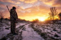 Chasse d'hiver pour des li?vres au lever de soleil Chasseur se d?pla?ant avec le fusil de chasse photo libre de droits