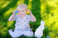 Chasse de petit garçon pour le jardin d'oeuf de pâques au printemps le jour de Pâques Images stock