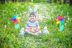 Chasse de petit garçon pour le jardin d'oeuf de pâques au printemps le jour de Pâques Petit enfant mignon avec le lapin tradition photo stock