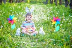 Chasse de petit garçon pour le jardin d'oeuf de pâques au printemps le jour de Pâques Petit enfant mignon avec le lapin tradition photographie stock libre de droits