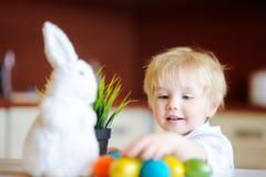 Chasse mignonne d'enfant d'enfant en bas âge pour l'oeuf de pâques le jour de Pâques Photographie stock libre de droits