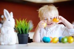 Chasse mignonne d'enfant d'enfant en bas âge pour l'oeuf de pâques le jour de Pâques Photographie stock