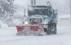 Chasse-neige avec une charrue rouge fonctionnant dans une tempête de neige images libres de droits