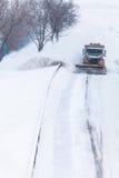 Chasse-neige enlevant la neige de la route pendant une tempête de neige Image stock