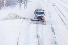Chasse-neige enlevant la neige de la route pendant une tempête de neige Image libre de droits