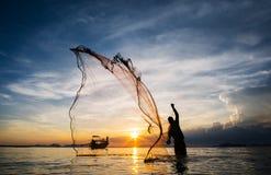 Chasse pour le coucher du soleil Silhouette de filet de pêche non identifié de bâti de pêcheur images stock