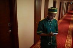 Chasseur écoutant la musique dans l'hôtel Hall image stock