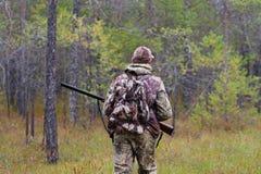 Chasseur avec l'arme à feu dans la forêt photos stock