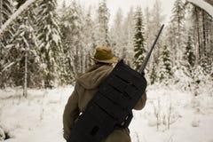 Chasseur avec l'arme à feu dans la forêt d'hiver Image stock
