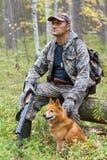 Chasseur avec le chien se reposant sur un arbre tombé image stock