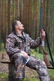 Chasseur avec le fusil de chasse dans le camp de forêt image stock