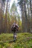 Chasseur avec une arme à feu dans une forêt de pin photo stock