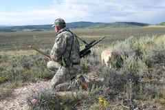 Chasseur dans le camouflage balayant un paysage aride photographie stock