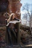 Chasseur de fille avec une arbalète sur les ruines photo stock
