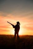 Chasseur féminin dans le coucher du soleil Image libre de droits