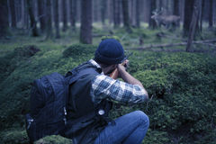 Chasseur interracial dans la forêt visant la proie Photos stock